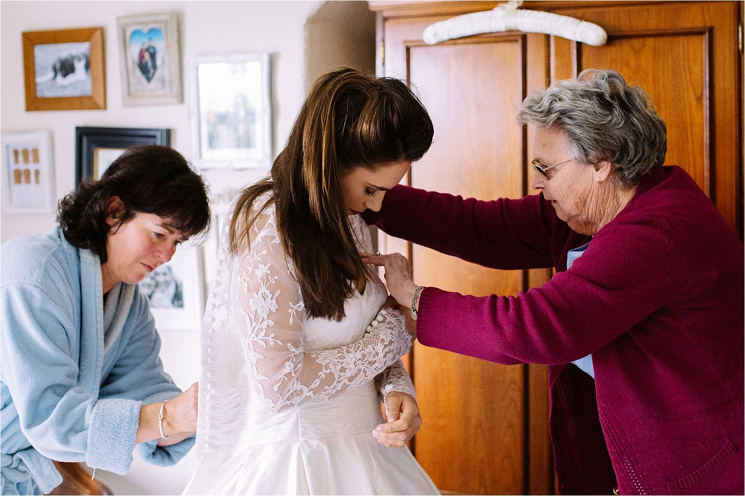 Bride being dressed by her mother and grandmother for her Prestbury wedding