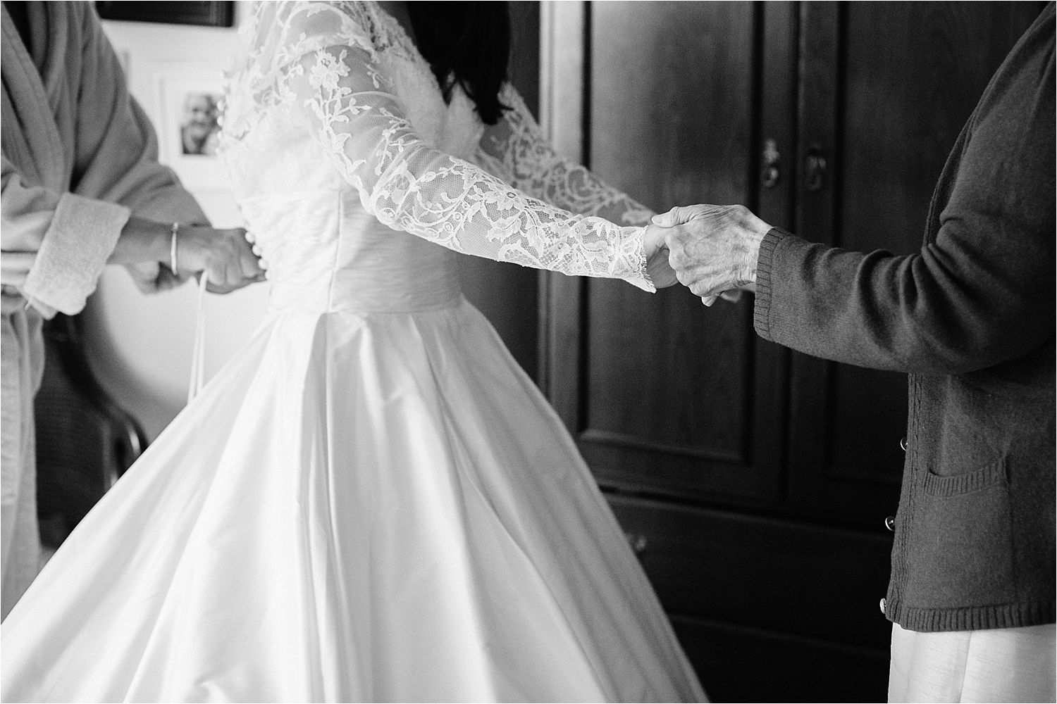 Bride and her grandmother holding hands as bride is buttoned into her wedding dress in Cheshire