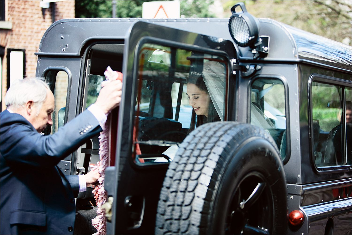 Prestbury bride is helped out of Landrover Defender at church