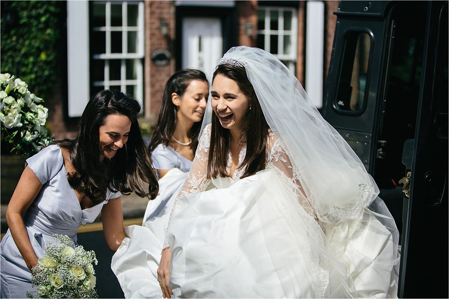 Bridesmaids help bride with her dress as she steps out of a Landrover Defender at St Peter's church in Prestbury