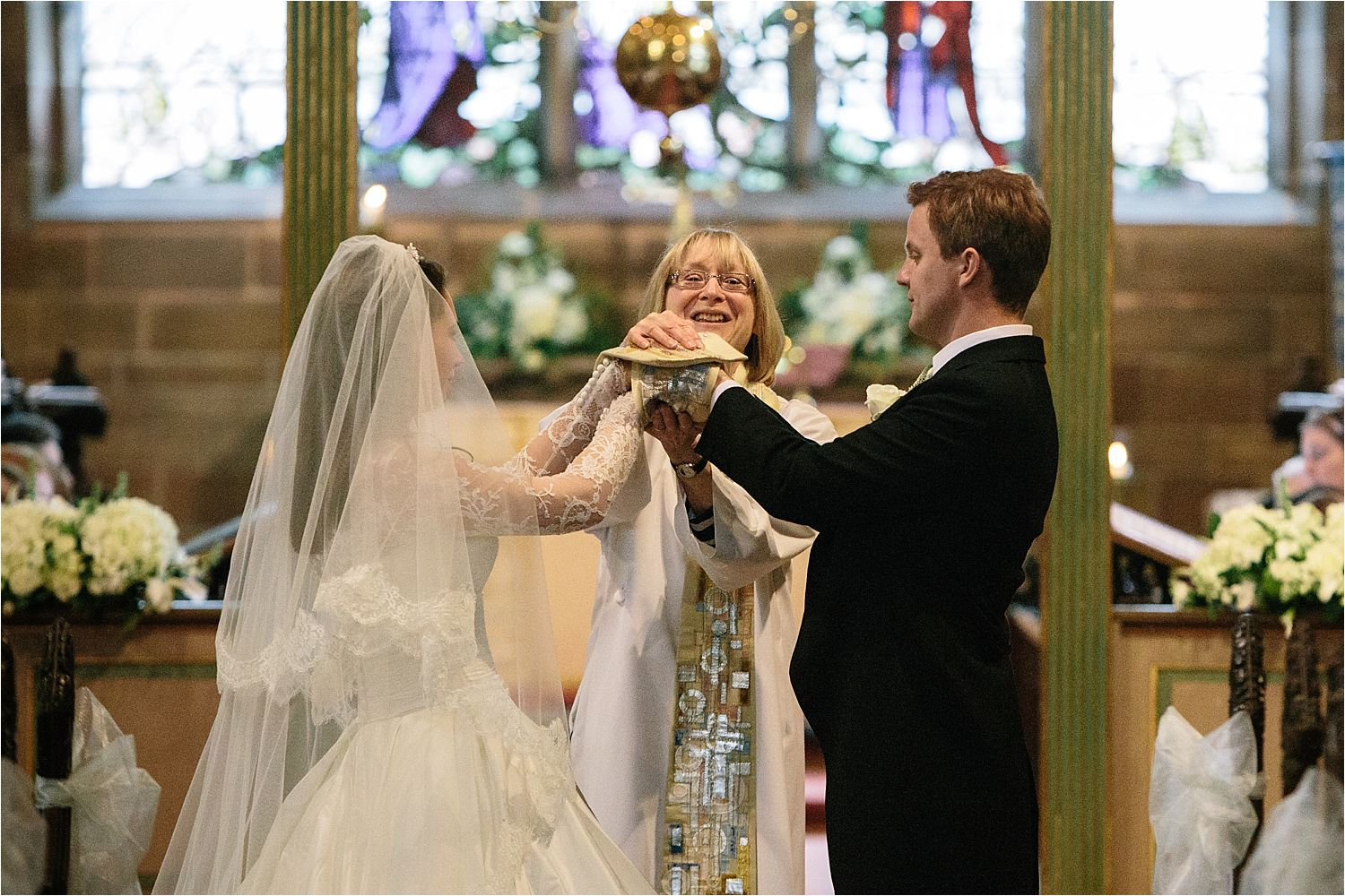 Lady vicar at St Peter's in Prestbury wraps the hands of the bride and groom