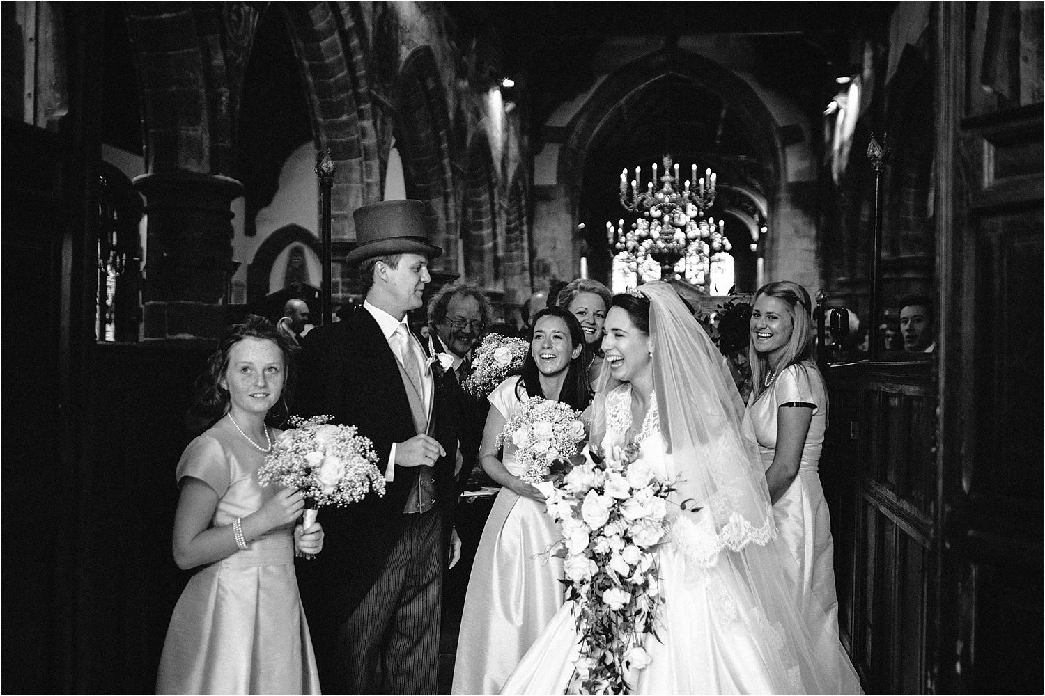 Laughing wedding group at St Peter's church Prestbury
