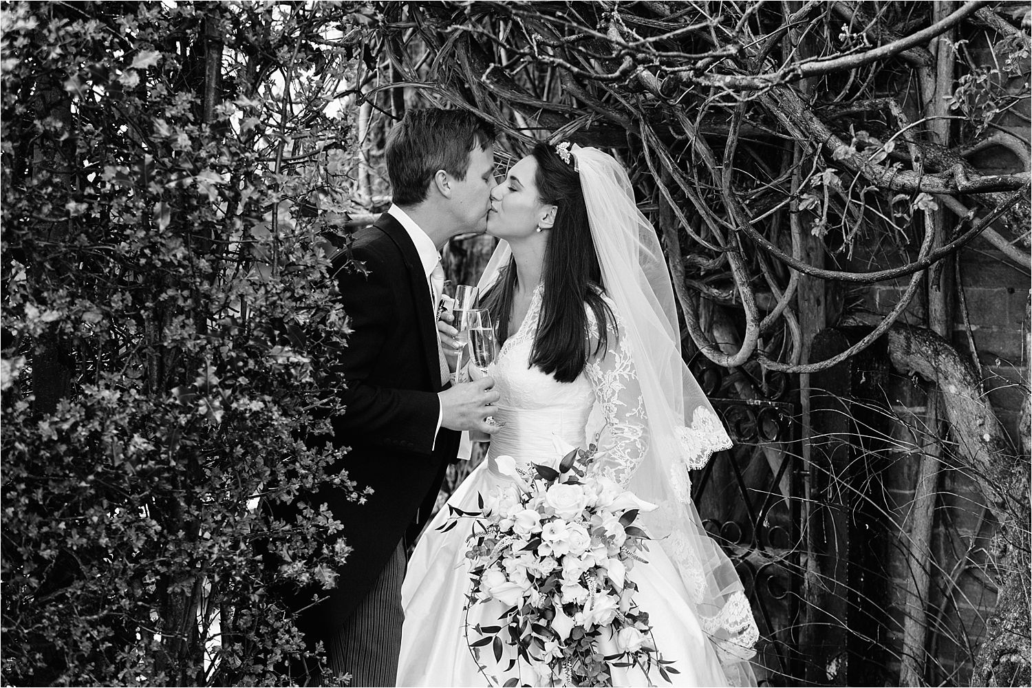 Bride and groom with champagne, share a kiss  in the grounds of Hilltop Counttry House