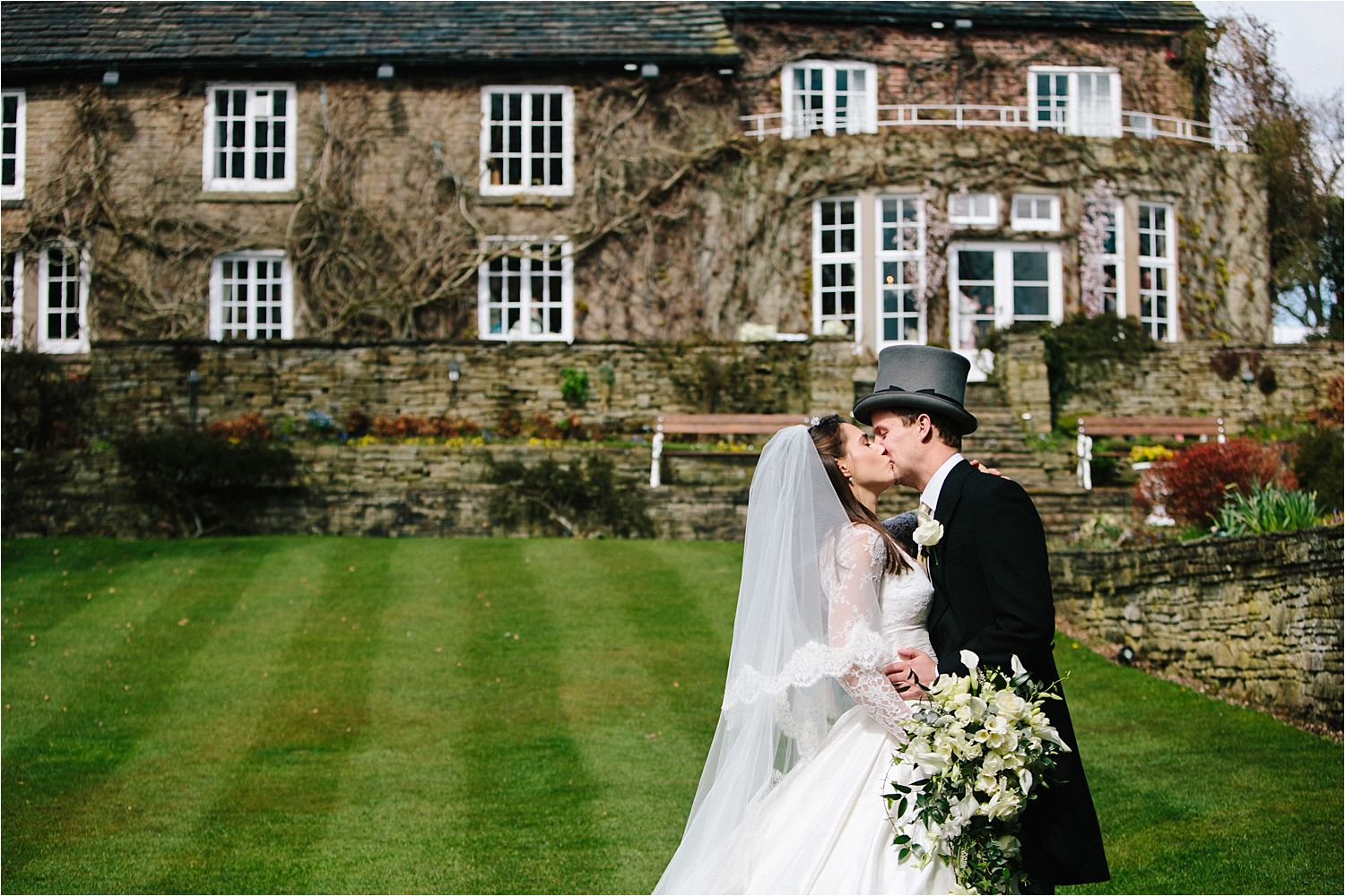 Bride and groom exchange a kiss in the gardens of Hilltop Country House in Cheshire