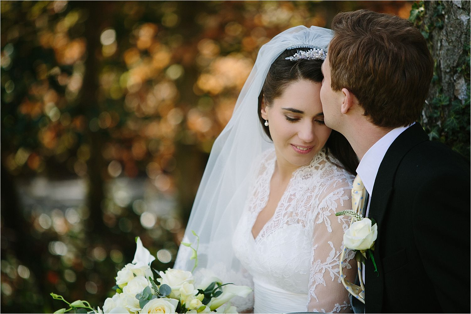Groom kisses his beautiful bride's forehead in the grounds of Cheshire wedding venue, Hilltop House