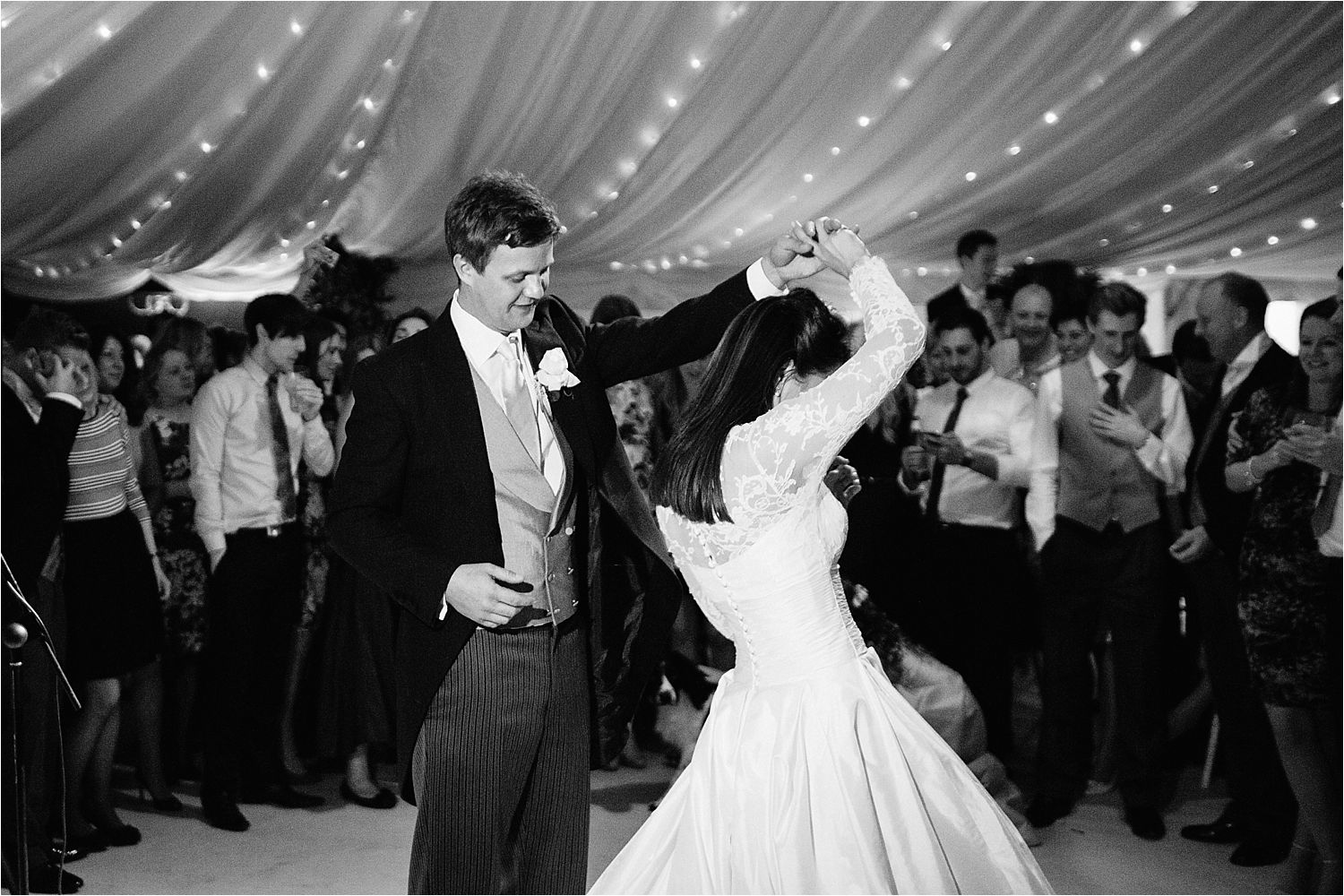 Bride and groom  do a twirl at their marquee wedding in Cheshire