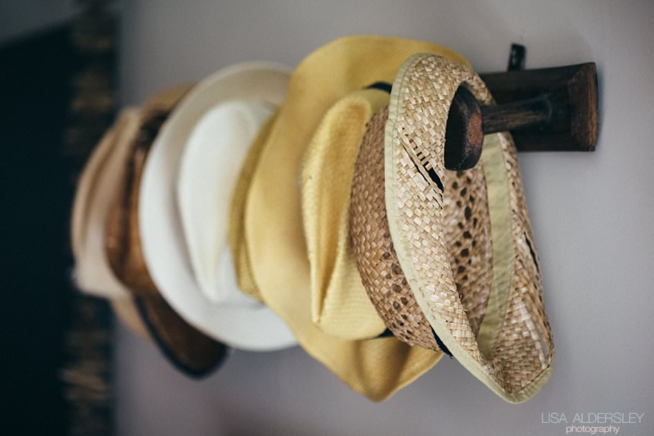 Lots of straw hats on pegs