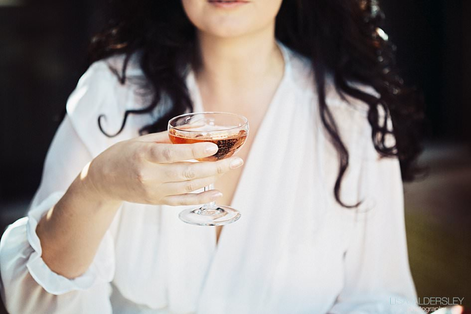 bride holding a glass of pink champagne