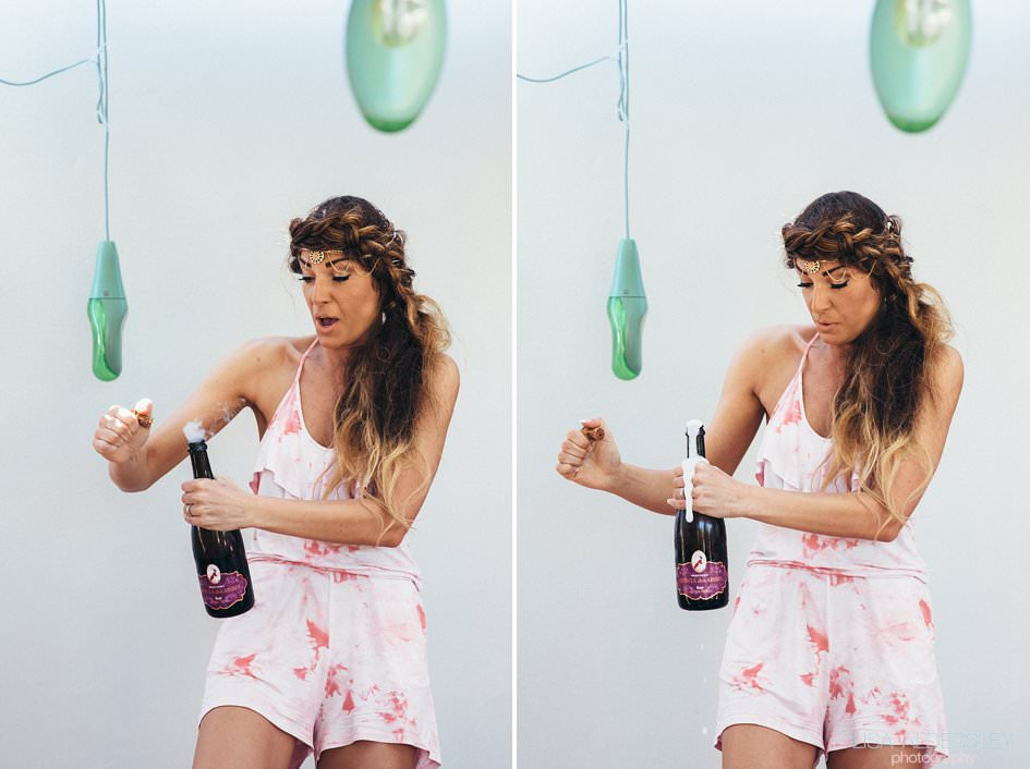 bridesmaid opening a bottle of champagne