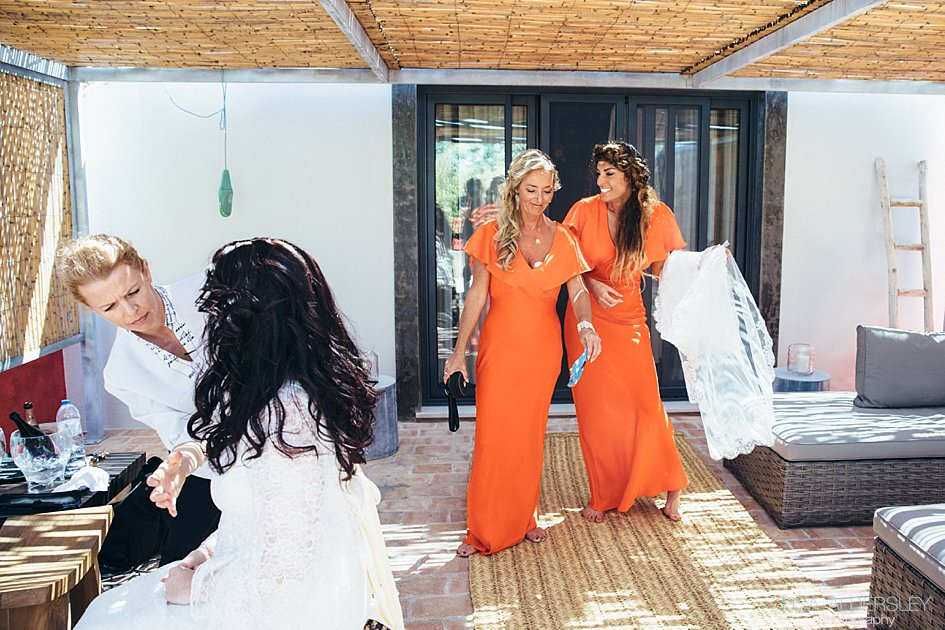 Bridesmaids emerging from the bedroom laughing, dressed in orange bridesmaid dresses from Top Shop