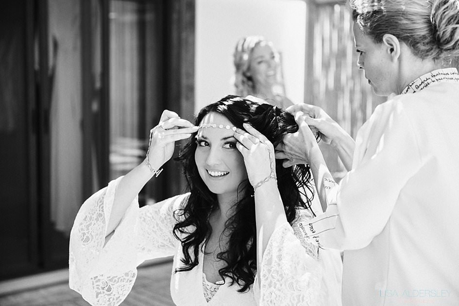 smiling bride trying to place her headpiece