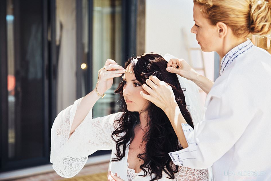 Bride holding her headpiece in place as the hairdresser fixes clips