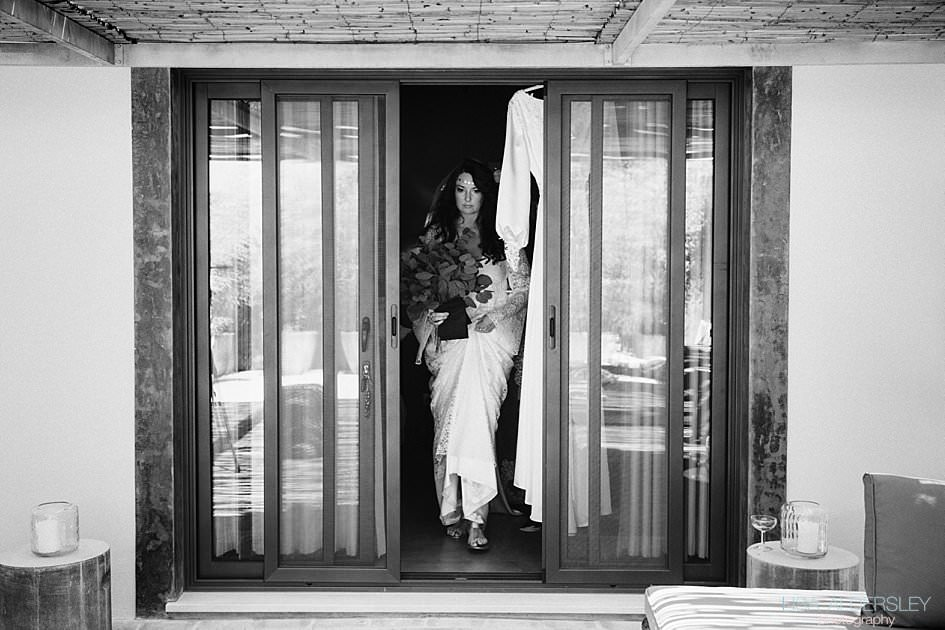 Bride emerging from bedroom dressed in her charlie brear wedding gown