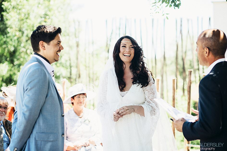 Groom and bride laughing with the celebrant during the wedding ceremony