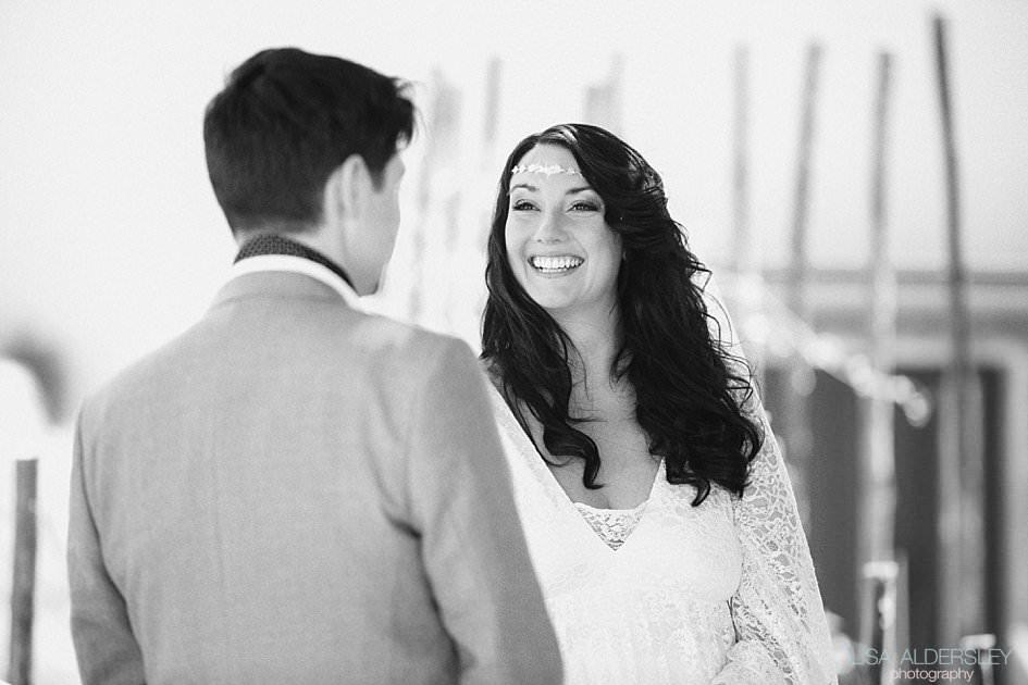 Bride looking and laughing at her husband to be during the ceremony