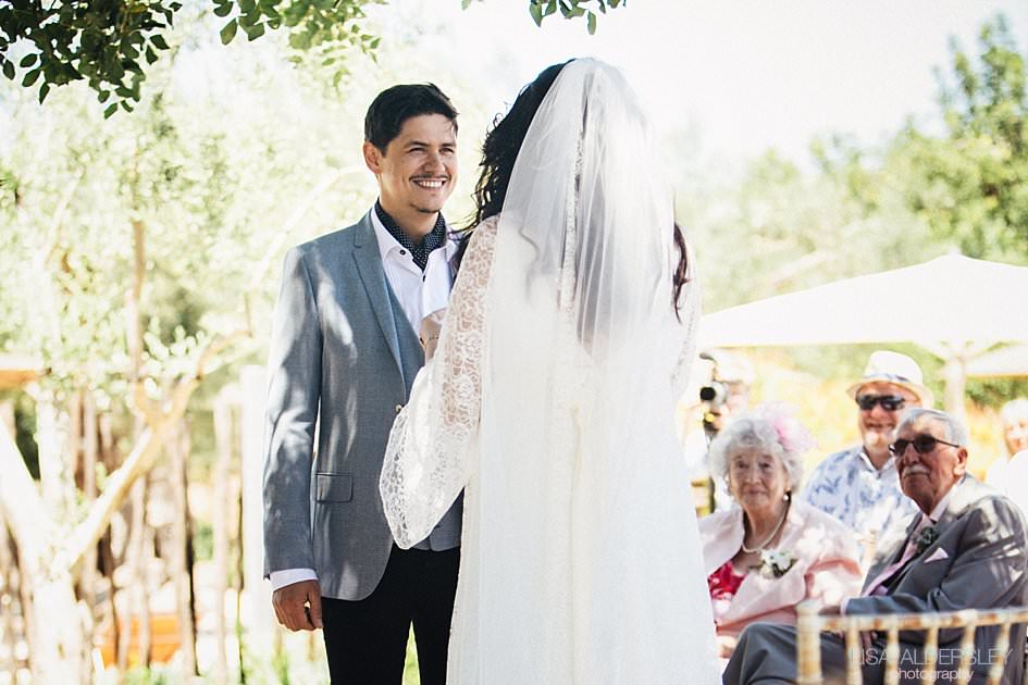 Groom smiling at his wife to be as she says her vows