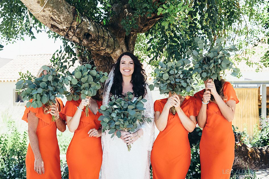 Bride and her bridesmaids laughing and hiding behind their bouquets