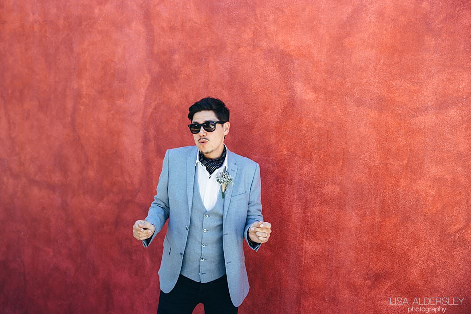 Groom dancing against a pomegranite coloured wall