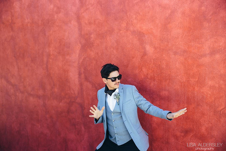 Groom dancing and being silly against a pomegranite coloured wall