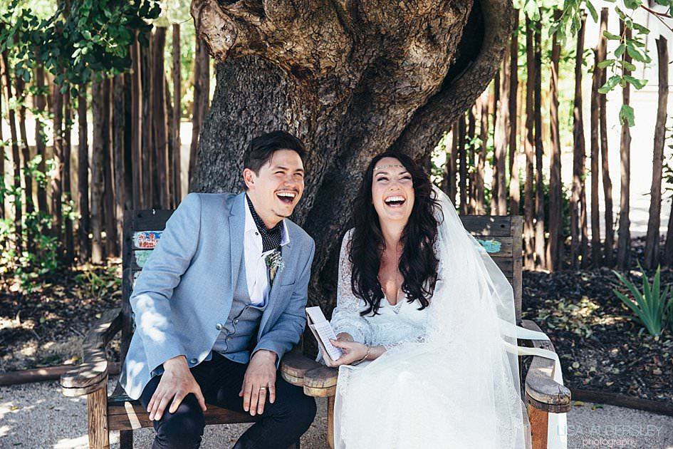 Bride and groom sat by an olive tree laughing