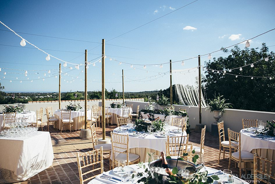 Roof terrace set up with tables, chairs and edison lights for the wedding dinner
