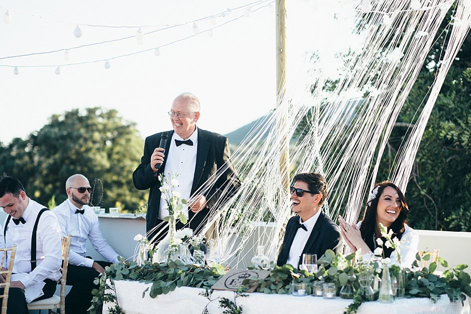 Brides father doing a speech as bride and groom laugh at what he's saying