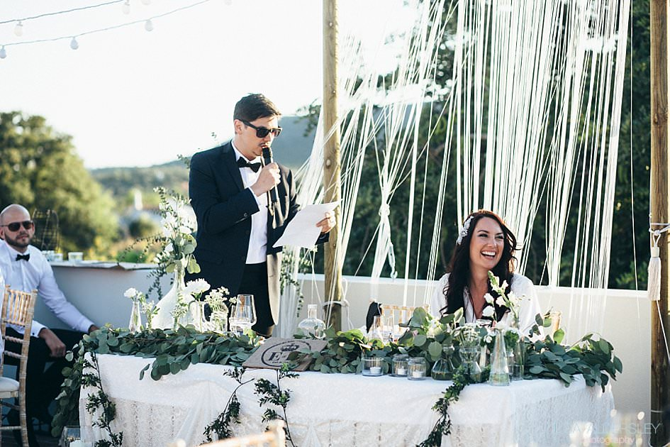 Bride laughing as groom reads his speech