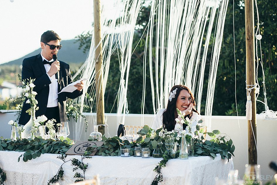Groom reading his speech as bride smiles
