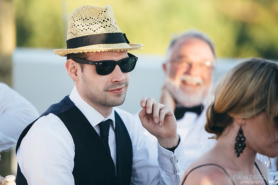 Wedding guest in black tie and a straw hat