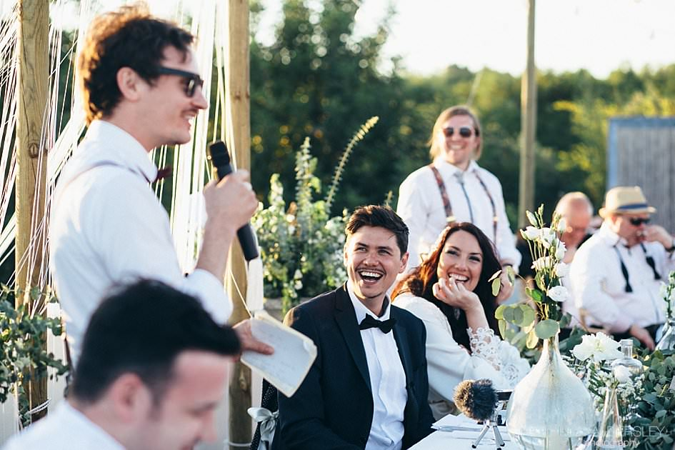 Couple laughing as bestman delivers his speech