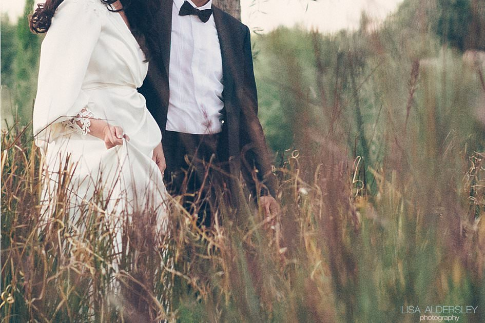 Bride holding her dress walking through long grass