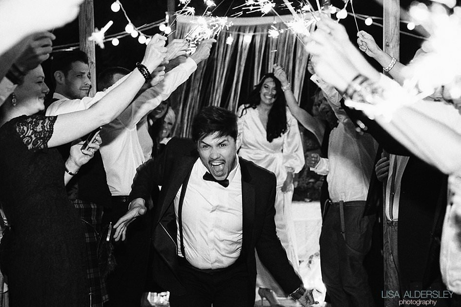 Groom running through a tunnel of guests holding sparklers