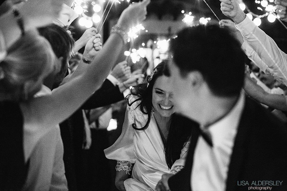 Bride and groom running through a tunnel of guests holding sparklers