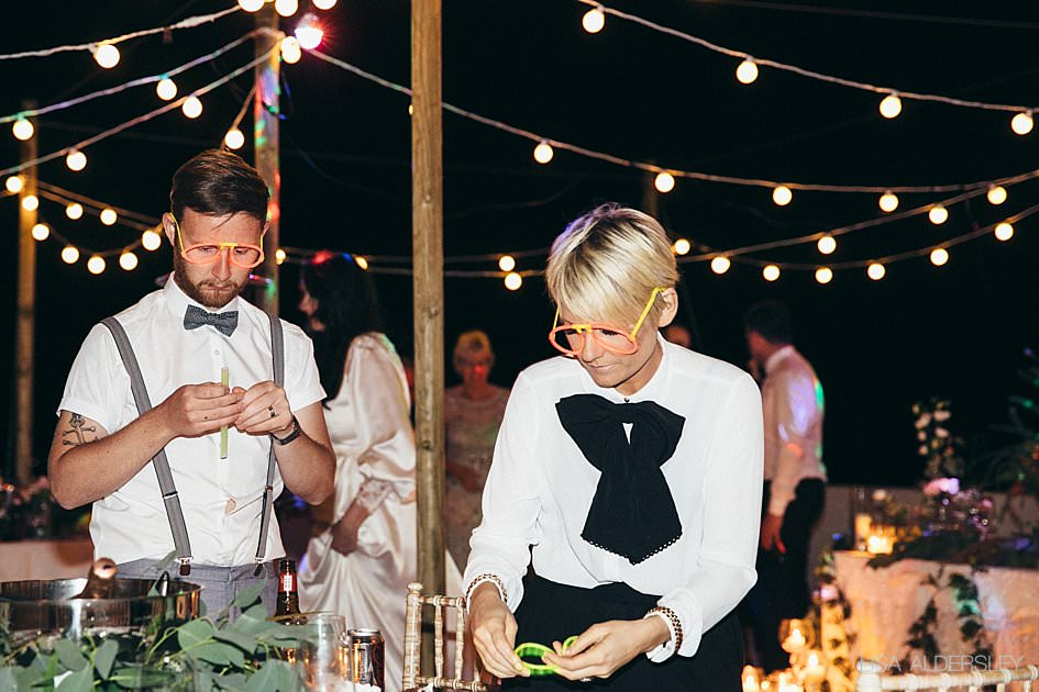 Wedding guests dressing up in glow glasses