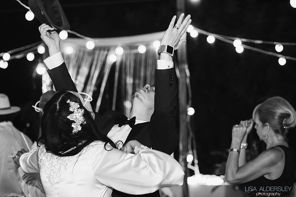 Bride and groom dancing. Groom raises his hands in the air