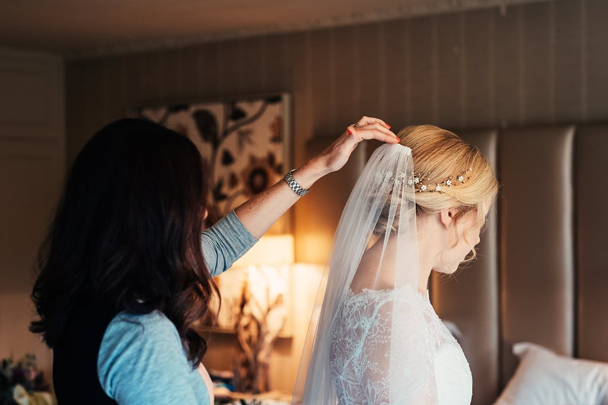 Hairdresser fixing the brides veil into her hair