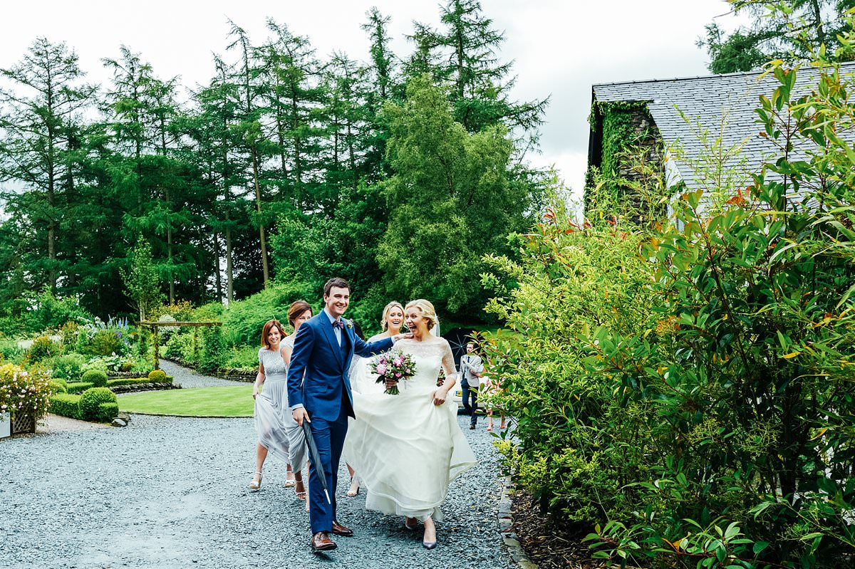 Bride and groom walking down the path with their guests following