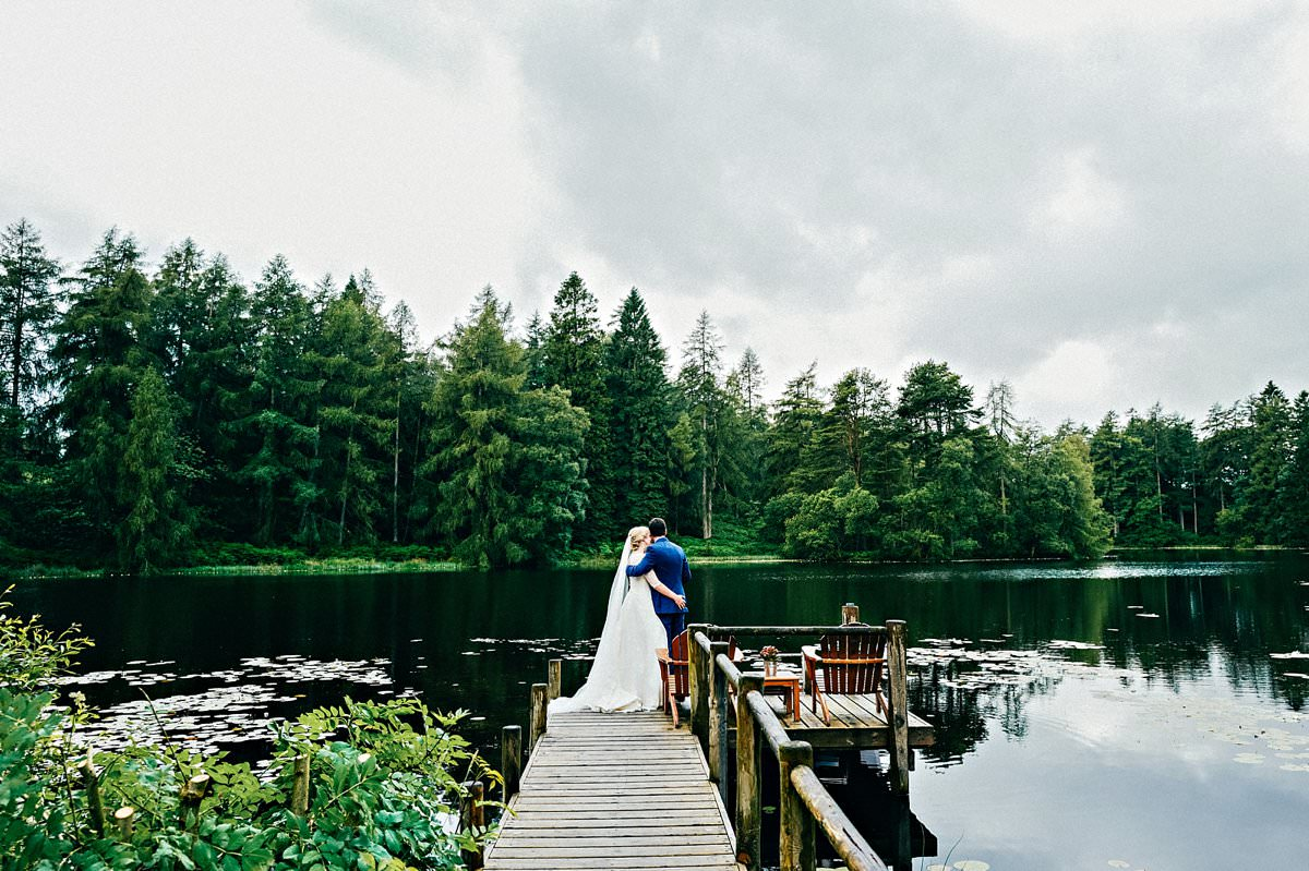 Bride and groom overlooking Knipe Tarn at Gilpin hotel and Lake House