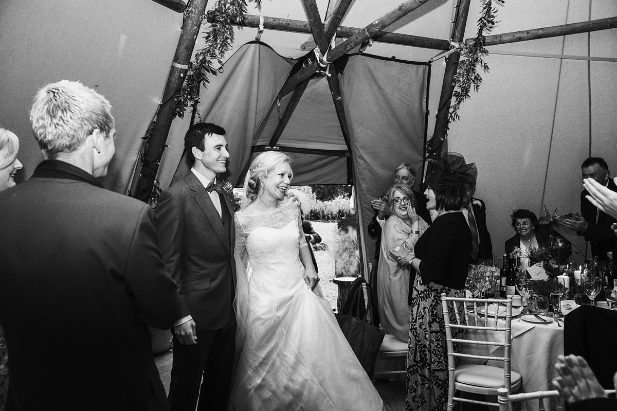 Bride and groom entering the Teepee as guest look on clapping