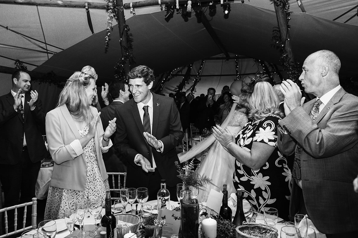 Guests clapping and smiling as the bride and groom enter the marquee