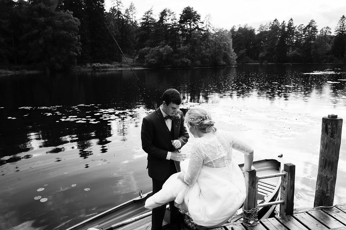 Bride and groom getting into a rowing boat