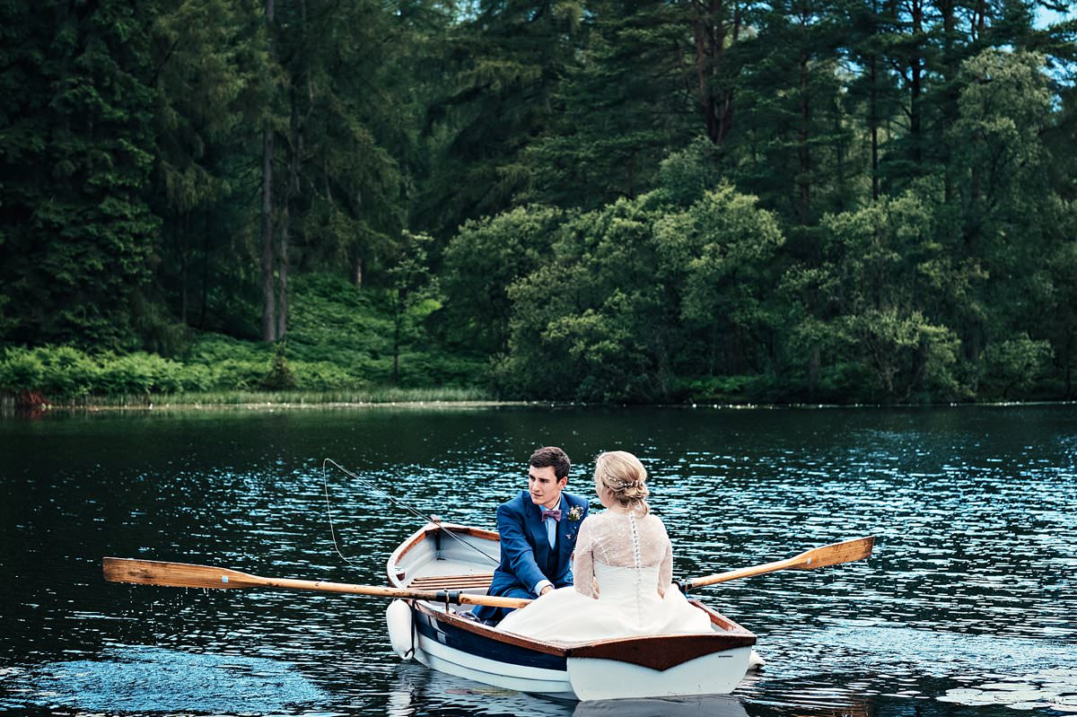 Bride and groom in the rowing boat at Gilpin Lake house