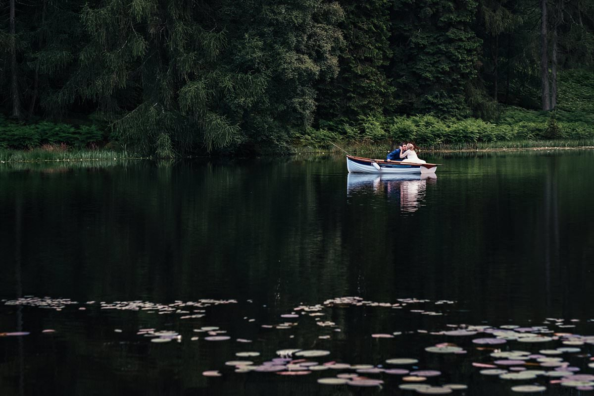 Bride and groom kissing in a rowing boat at Gilpin Lake House