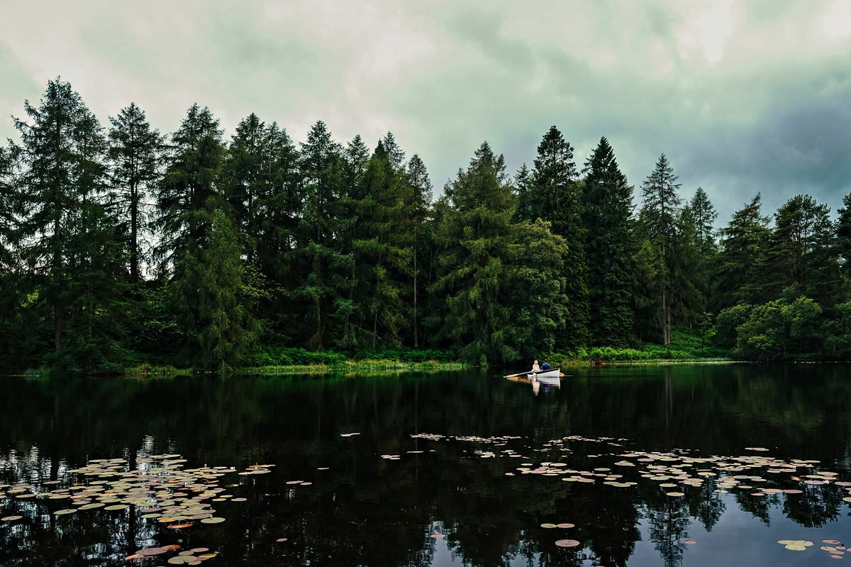Bride and Groom in a rowing boat on Knipe Tarn at Gilpin Hotel and Lake House
