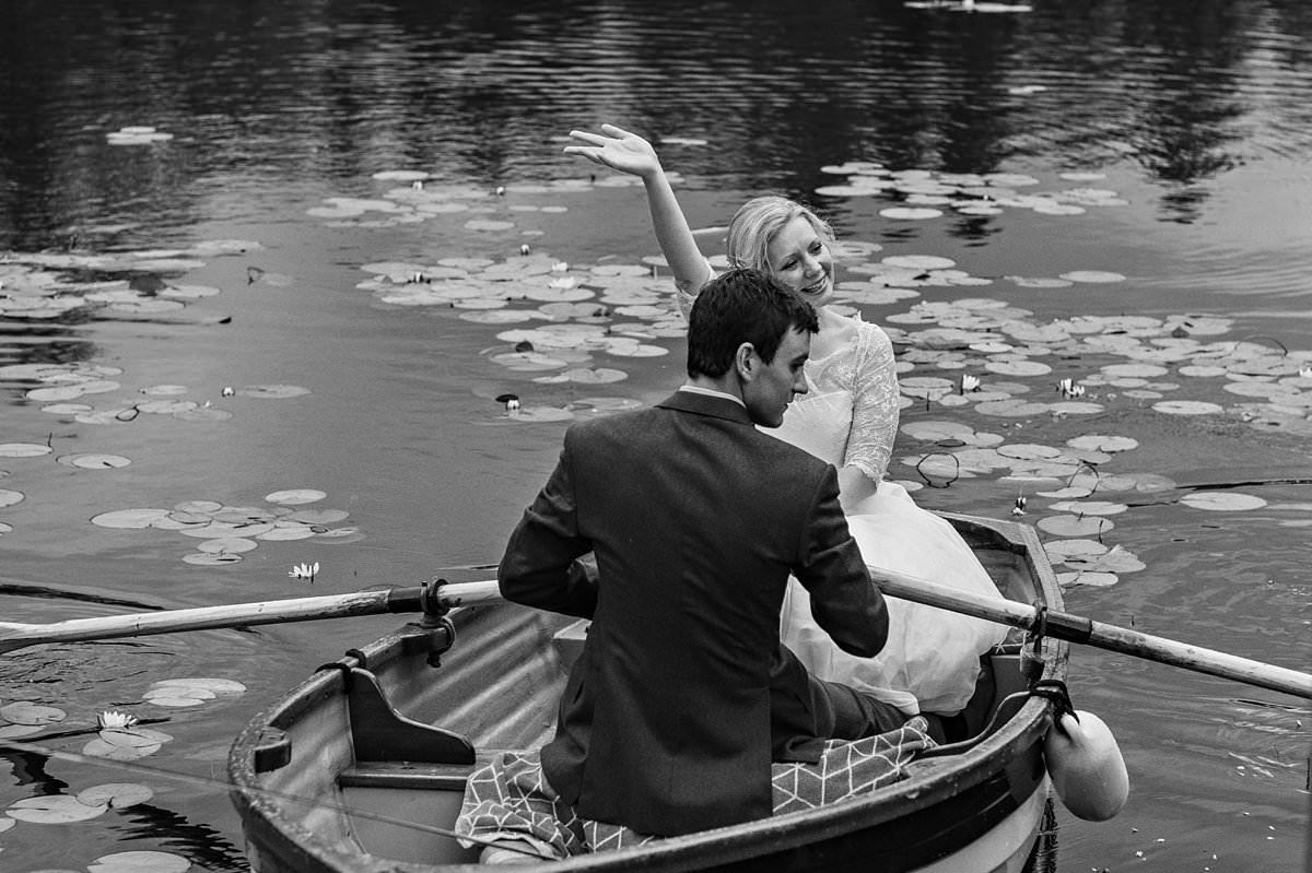 Bride waving at her guests from a rowing boat as the groom steers them back into shore