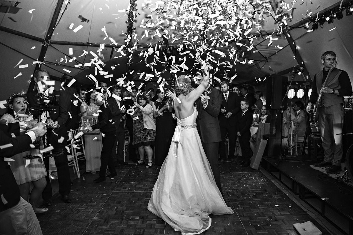 Bride and groom doing their first dance under the confetti shower