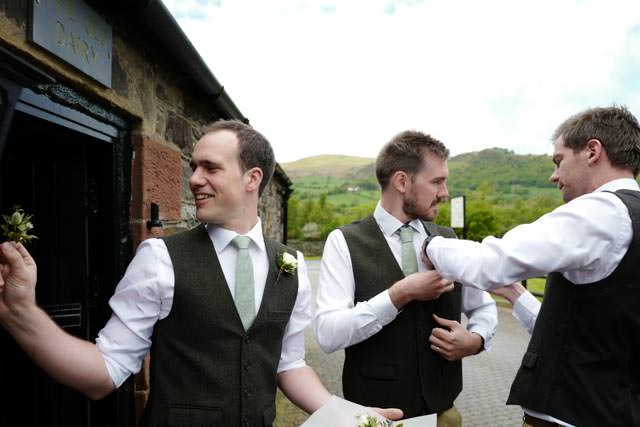 Groomsmen attaching their buttonholes