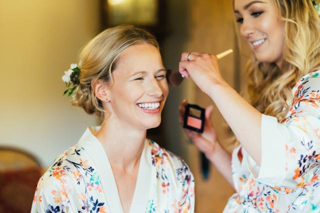 Bride having her makeup done by her bridesmaid