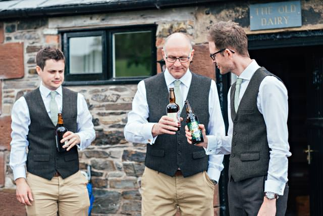 Groom and father of the bride clinking bottles