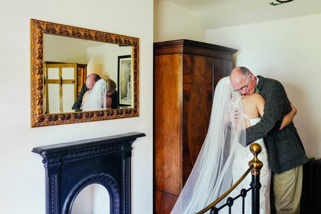Brides dad hugging her after he sees her in her dress for the first time